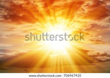 Bright sun in the orange sky with cumulus clouds #706967410