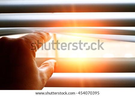 Bright sun shining through a jalousie #454070395