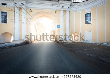 Bright sunlight breaks through classic white and yellow tones arch. Building with large and two small arches and windows. Street road in main arch. Winter in city.