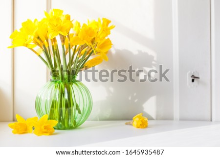 bright sunlight shines on Easter bells, daffodils flowers in vase on the windowsill. country style bouquet for spring decoration or Easter decoration against open background with copy space