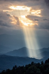 Bright sunlight shining through hole of clouds to dark scene of mountain range before sunset in Thailand rainforest area.