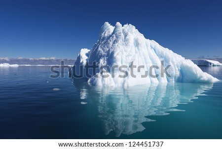 Stock Photo Bright sunny day in Antarctica. Full calm and reflection of icebergs in deep clear water. Travel by the ship among ices. Snow and ices of the Antarctic islands.