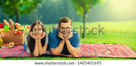 Bright sunny photo of young happy couple, lying together on a picnic blanket, with basket, outdoor. Copy space empty place for some text, advertising or slogan.  Stok fotoğraf ©