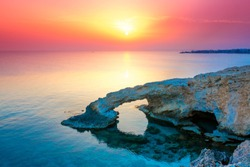 Bright sunny pink sunset against the background of a rocky arch bridge in the city of Ayia Napa bridge of lovers at dusk. Travel to Cyprus tourism to the sights of the island