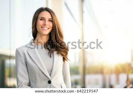 Bright sunny vibrant portrait of beautiful woman business executive style in downtown urban area
