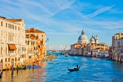 Bright sunny view of The Grand Canal with gondola the Santa Maria della Salute church, Venice, Italy