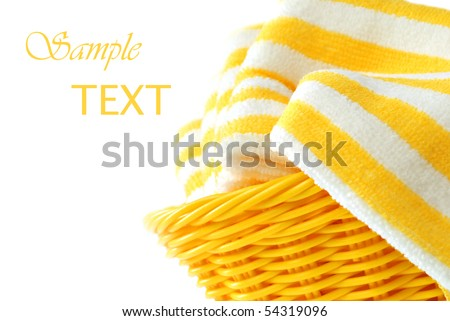 Bright sunny wicker basket filled with fresh clean towels.  Close-up on white background with copy space.