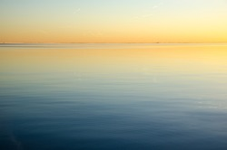 Bright sunset colors in the sky and in the calm smooth water