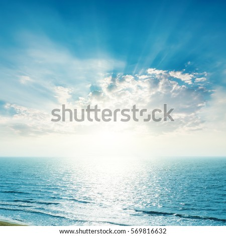 bright sunset in blue sky with clouds over sea #569816632