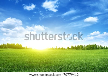 Bright sunset over green field. #70779412