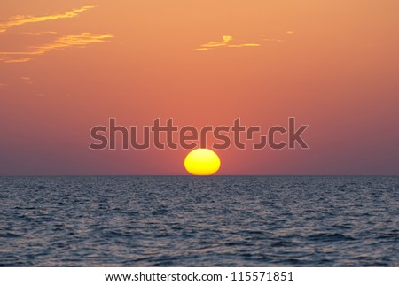 Bright sunset under the sea with yellow red gradient colors - stock photo