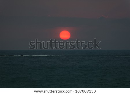 Bright sunset with large red sun under the ocean surface and wave foam