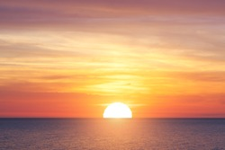Bright sunset with large yellow sun under the sea surface
