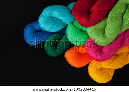 Bright thread in skeins, yarn in bright colors, set of yarn on black background, cotton, linen, flax, skein, yarn