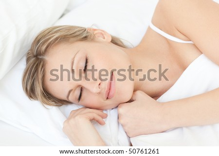 Bright tired woman sleeping on her bed at home