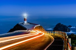 Bright trailing car lights lead to Cabo Ortegal lighthouse at night