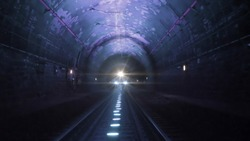 Bright train lights coming towards camera in a dark railway tunnel
