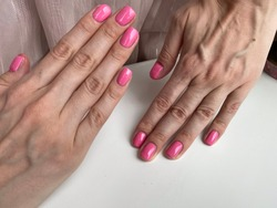 Bright trendy pink polished nails at home. Young woman showing off her perfectly shaped nails.