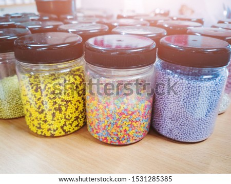 Bright varied confectionery topping for desserts in jars in a cafe. The concept of sweets, food chopping.