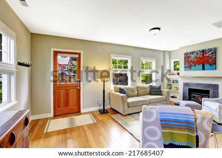Bright very small room with fireplace, sofa and armchair. View of entrance door with rug on hardwood floor