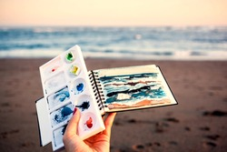Bright watercolor limited palette, ready sketch of sea landscape in a female artist's hand on a beach at sunset