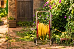 Bright watering garden hose near old stone house