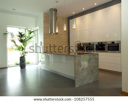 Bright well designed kitchen with travertine wall