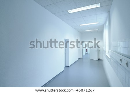 Bright white clean corridor with red fire extinguisher on wall. Space for copy.