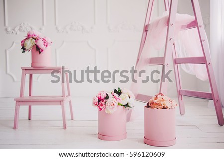 Bright white interior with lots of pink flowers. Pink powder. Bouquet of delicate pink flowers in round boxes. Stairs and chair on the white wooden floor with lots of bouquets of pink flowers.