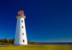 Bright white Lighthouse against deep blue sky