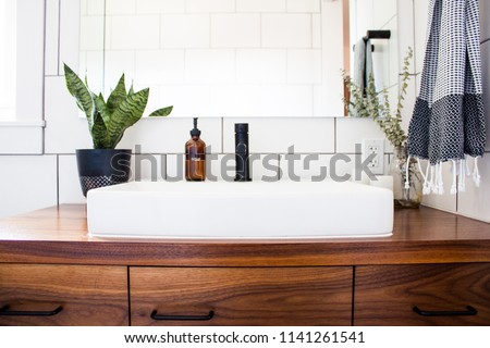 Bright white modern bathroom sink and vanity with plants and soap dispenser and mirror and towel in natural light filled all white modern bathroom.