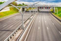 Bright wide high speed highway against distant industrial landscape and dramatic sky. HDR style image