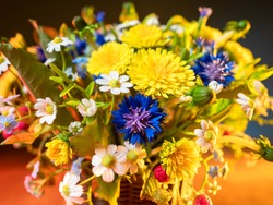 Bright wildflowers close-up. Nature's bounty. Russian bouquet. The beauty of wild flowers. Basket of flowers and berries in bright lighting. Rustic bouquet.