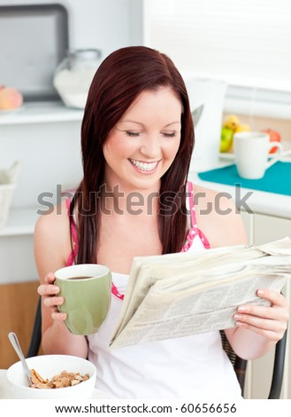 Bright woman eating cereals while reading newspaper in the kitchen at home