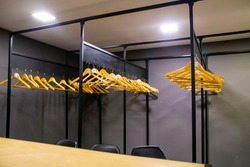 bright wooden hangers with numbers in empty cloakroom or checkroom or wardrobe