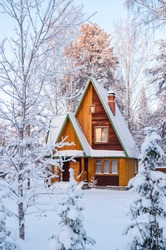 Bright wooden house in the snow-covered forest. Ural, Russia.