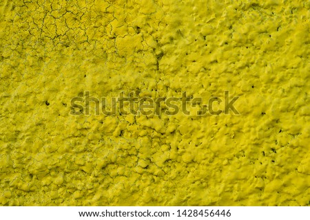 Bright yellow background texture. Macro photo of a rough, rough, cracked wall surface painted with yellow paint.