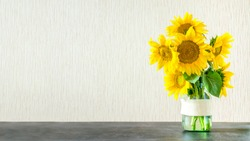 Bright yellow big sunflowers in glass vase on dark table on light texture background. Mockup banner with sunflower bouquet with copy space.