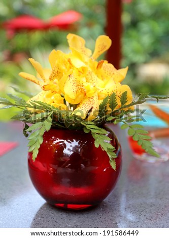 bright yellow bouquet of orchids in a red glass vase on the table