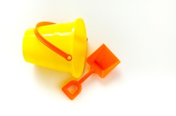 bright yellow child's sand pail on its side with a bright orange shovel isolated on white