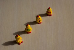 bright yellow Easter chickens four pieces stand on a light wooden background lit by the sun with a shadow