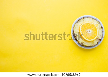 Bright yellow one-color background with slices of orange, pineapple, top view. Travel or tourism concept. Space for a text or product display. #1026588967