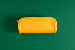 Bright yellow school pencil case, accessories on green background. Back to school. Flat lay, top view, copy space
