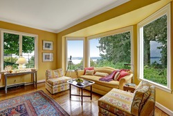 Bright yellow sitting area with wide window and yellow sofa and chairs