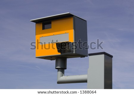 Bright yellow speed trap camera on grey / gray metal post. Blue sky background.