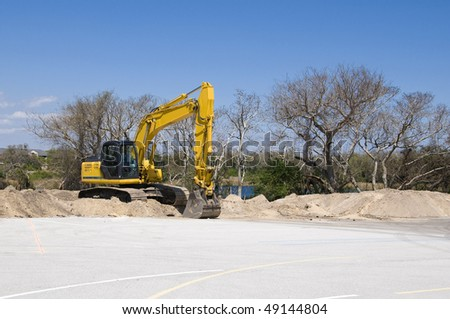 Bright yellow tract backhoe with blue sky