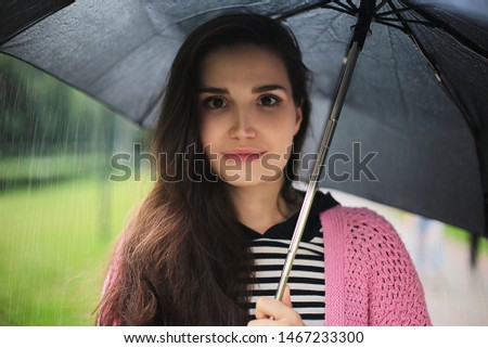 Bright young girl with dark hair and brown eyes in a striped sweater and knitted pink cardigan with a black umbrella in the rain on nature walking path good mood autumn damp weather