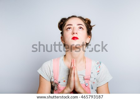 Bright young woman praying, dressed in a pink overalls, isolated on white background #465793187