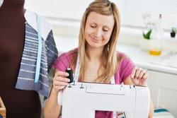 Bright young woman using her sewing machine in the kitchen