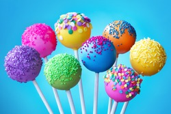 Brightly colored cake pops on a blue background